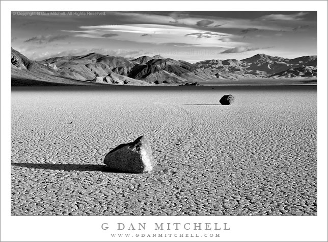 """Two Rocks, Morning, Racetrack Playa - Black and white photograph of two """"moving rocks"""" on the Racetrack Playa at Death Valley National Park. Morning light with unusual clouds, and the Grandstand in the distance."""