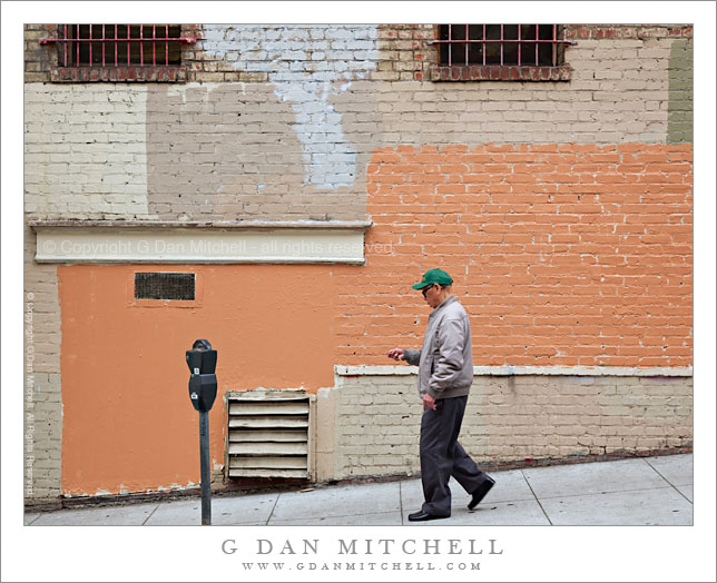 Man Walking Past Painted Brick Wall