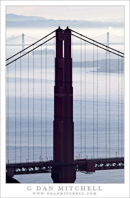 North Tower of the Golden Gate Bridge, San Francisco Bay, Morning - The north tower of the Golden Gate Bridge, with San Francisco Bay, the San Francisco Oakland Bay Bridge, a departing ship, and the East Bay hills beyond in morning fog and haze.