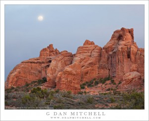 The full moon rises in a cloudy sky above sandstone towers, Arches National Park, Utah.